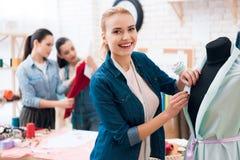 3 девушки на фабрике одежды Одно из их измеряет новое платье Стоковая Фотография RF