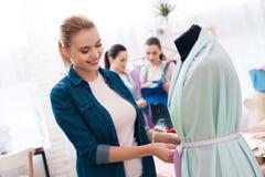 3 девушки на фабрике одежды Одно из их измеряет новое платье стоковое фото