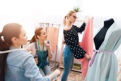 3 девушки на фабрике одежды Они обсуждают дизайн нового платья Стоковое Изображение