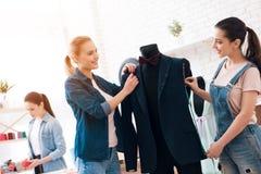 3 девушки на фабрике одежды Они обсуждают desing для новой куртки костюма Стоковая Фотография RF