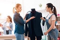 3 девушки на фабрике одежды Они обсуждают desing для новой куртки костюма Стоковые Фотографии RF