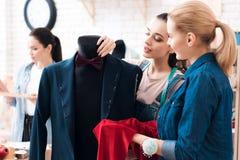 3 девушки на фабрике одежды Они обсуждают desing для новой куртки костюма Стоковые Изображения RF