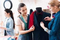 3 девушки на фабрике одежды с новым костюмом Одно из их держит ножницы Стоковые Фотографии RF