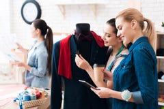 3 девушки на фабрике одежды с новым костюмом Одно из их держит ножницы Стоковое фото RF