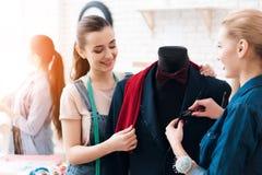 3 девушки на фабрике одежды с новым костюмом Одно из их держит ножницы Стоковое Изображение
