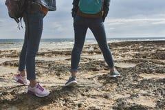 Девушки на seashore с рюкзаками Стоковая Фотография