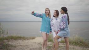 3 девушки нося длинное платье моды лета делая selfies на предпосылке озера или реки Кавказец 2 сток-видео