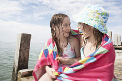 Девушки обернутые в полотенце сидя на моле Стоковая Фотография