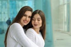 2 девушки обнимают на предпосылке стеклянного случая Стоковое Изображение RF