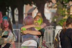 Девушки обнимая на цветах фестиваля Holi в городе Чебоксар, республики Chuvash, России 06/01/2016 Стоковое Фото