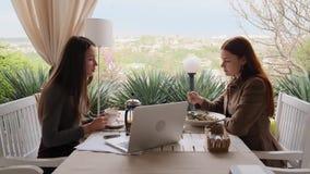 2 девушки обсуждают их вещи работы есть салаты и выпивая замедленное движение чая акции видеоматериалы