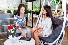 Девушки обсуждают листья уклада жизни места переговора друга женщин молодой подруги портрета 2 кафа дела успешные привлекательные Стоковые Изображения RF
