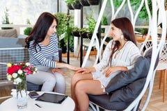 Девушки обсуждают листья уклада жизни места переговора друга женщин молодой подруги портрета 2 кафа дела успешные привлекательные Стоковая Фотография
