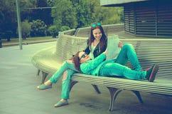 Девушки отдыхая на стенде в городе Стоковые Фото