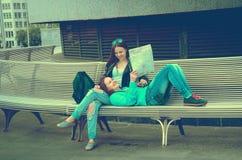 Девушки отдыхая на стенде Стоковое Фото