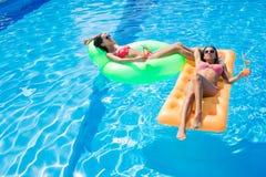 Девушки отдыхая на тюфяке воздуха в бассейне Стоковое Фото