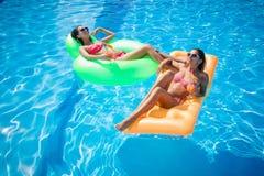 Девушки отдыхая на тюфяке воздуха в бассейне Стоковое Изображение