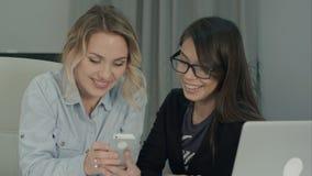 2 девушки офиса смеясь над и имея потехой смотря телефон Стоковые Изображения RF