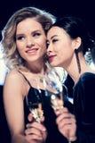 Девушки очарования многокультурные держа стекла шампанского и тратя время на партии Стоковая Фотография