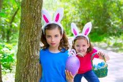 Девушки пасхи играя на лесе с зубами зайчика показывать Стоковые Фотографии RF