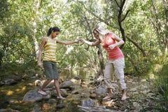 Девушки пересекая поток в лесе Стоковые Фотографии RF