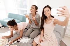 Девушки плачут на куриц-партийном Они сидят на кровати в комнате Девушки делают selfie Стоковые Изображения