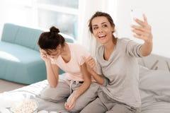 Девушки плачут на куриц-партийном Они сидят на кровати в комнате Девушки делают selfie Стоковые Изображения RF