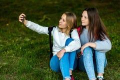 девушки подростковые 2 В лете парка города Они сидят на траве и принимают фото на smartphone За рюкзаками Стоковая Фотография RF