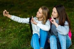девушки подростковые 2 В лете парка города Они сидят на траве и принимают фото на smartphone За рюкзаками Стоковые Изображения RF
