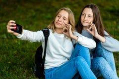 девушки подростковые 2 В лете в природе парка Сидите на траве за рюкзаками В его руках держит smartphone Примите фото Стоковые Фотографии RF