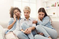 Девушки подслушивая ее мобильный телефон друга для того чтобы поговорить Стоковые Фотографии RF