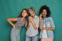 Девушки подслушивая их мобильный телефон друга для того чтобы поговорить Стоковое Изображение RF