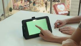 2 девушки показывают таблетку с зеленым экраном