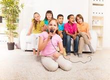 Девушки поя перед ее друзьями Стоковая Фотография RF
