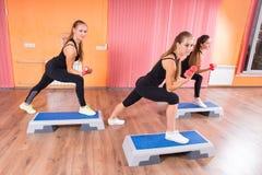 Девушки поднимая весы пока шагающ на платформы Стоковая Фотография
