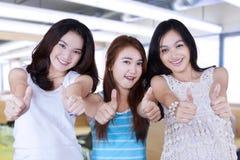 Девушки подростка давая большие пальцы руки вверх в классе Стоковые Изображения