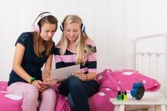 Девушки подростка с таблеткой и smartphone Стоковые Фотографии RF