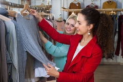 Девушки подруг выбирают одежды в магазине одежды Стоковое Изображение RF