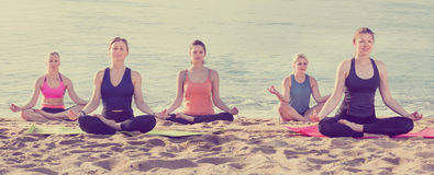Девушки практикуя йогу в положении лотоса на пляже Стоковое фото RF