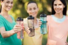 3 девушки представляя в парке кладя вперед их руки с бутылками спорт Стоковые Изображения