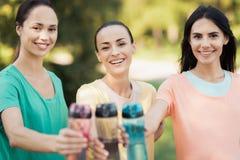 3 девушки представляя в парке кладя вперед их руки с бутылками спорт Стоковое фото RF