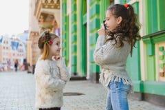 Девушки представляя и фотографируя на ретро камере в городе Стоковое Фото
