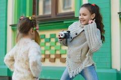 Девушки представляя и фотографируя на ретро камере в городе Стоковые Фото