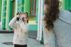 Девушки представляя и фотографируя на ретро камере в городе Стоковое Изображение RF