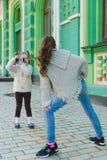 Девушки представляя и фотографируя на ретро камере в городе Стоковая Фотография