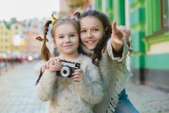 Девушки представляя и фотографируя на ретро камере в городе Стоковые Фотографии RF