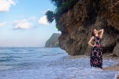 Девушки представляя на пляже перед утесом Стоковое Фото