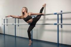 Девушки пригонки подготавливая разминку ног Нога протягивая женщину фитнеса тренировки делая подогрев, мышцы подколенного сухожил стоковая фотография