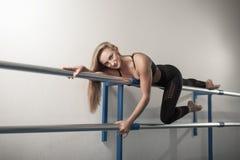 Девушки пригонки подготавливая разминку ног Нога протягивая женщину фитнеса тренировки делая подогрев, мышцы подколенного сухожил стоковая фотография rf