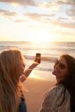 Девушки принимая фото захода солнца с мобильным телефоном Стоковое Изображение RF